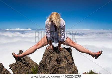 Young blonde woman acrobat making splits on rock on mountain's summit.