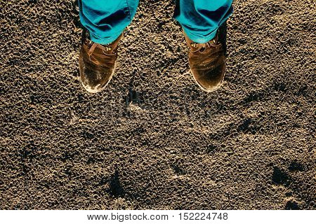 Male shoes on textured sand contrast blue trousers.
