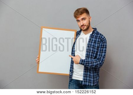 Portrait of a smiling casual bearded man pointing finger at blank board isolated on a gray background