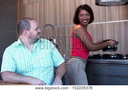 overweight man sitting at kitchen table and hispanic woman is cooking