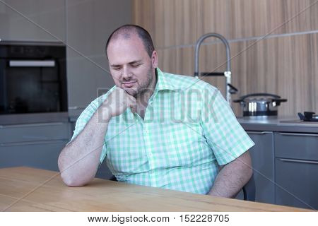 portrait of overweight man sitting at kitchen table with his eyes closed