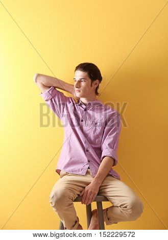 Handsome young man sitting on stool on yellow background