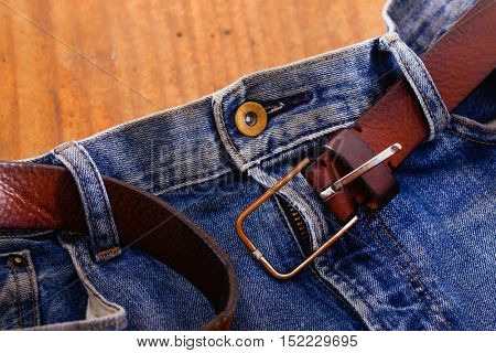 the old blue jeans and leather belt on wood background