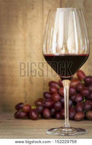 Red wine and grapes, over warm timber background.