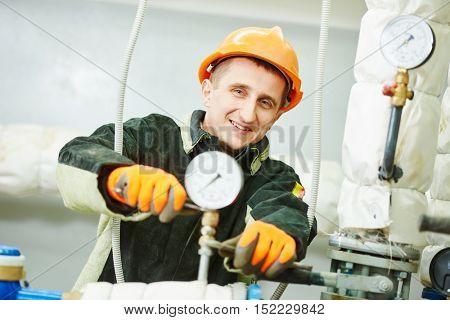 worker fixing manometer in boiler room