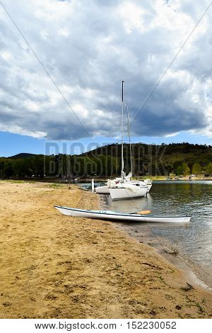 Two yachts and one kayak moored by the lakes shore on a cloudy day