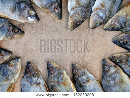 Many dried perches arranged in a circle on the wooden background. River fish close up. Place for an inscription