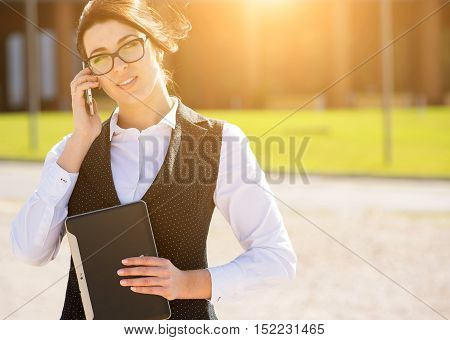 Portrait of a young smiling business woman with phone
