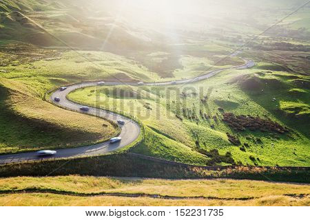 Scenic Serpentine Road with Cars in Golden Sunset Light