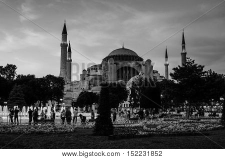 Hagia Sophia at sunset with motion blurred people walking by and illuminated fountain. Istanbul Turkey. Black and white