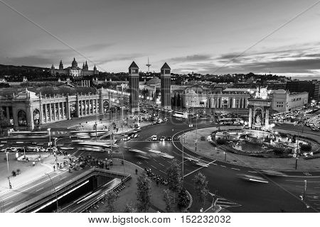 Spanish Square aerial view in Barcelona Spain at night. This is the famous place with traffic light trails fountain and Venetian towers and National museum at the background. Black and white