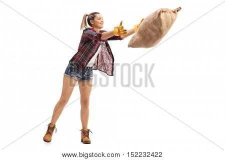 Full length portrait of a female agricultural worker throwing a burlap sack isolated on white background