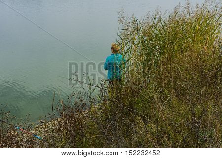 Lake in the mountains. Early morning. Woman fishing