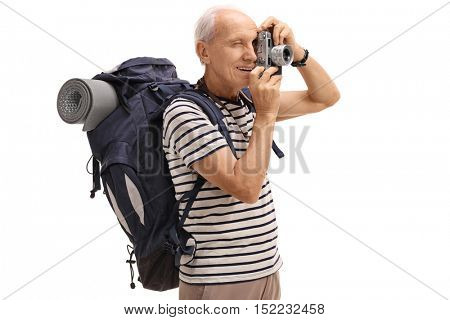 Elderly male hiker taking a picture with a camera isolated on white background