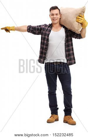 Full length portrait of a male farmer holding a burlap sack and pointing isolated on white background