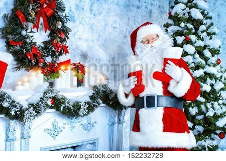 Santa Claus standing by the fireplace and Christmas tree in a beautiful room, decorated for Christmas. He puts Christmas gifts in socks.