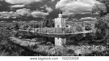Church Intercession on Nerl River 12th century Golden Ring tour Bogolyubovo Vladimir Russia. Panoramic view with reflection and cloudy sky. Black and white