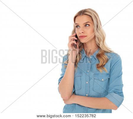 pensive blond woman speaking on the phone is looking up to her side on white background