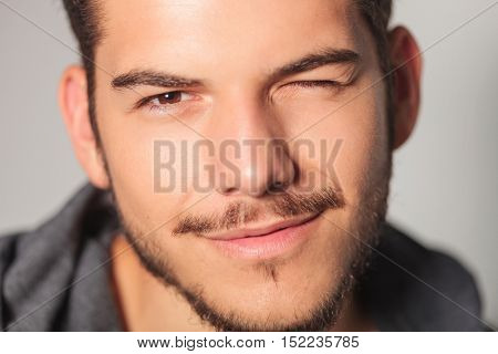 smilling young man is winking his eye , closeup picture in studio