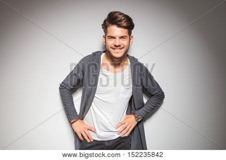 smiling young casual man with hands on waist posing against studio wall