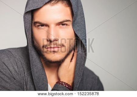 young casual man with hoodie on holding hand on neck , studio picture