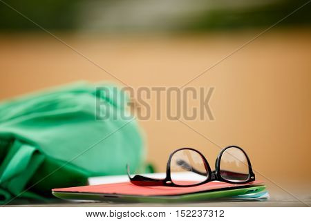 Backpack with glasses and book lying on wooden board, blurred background.Accessories for student