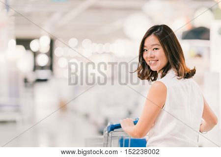 Beautiful young Asian woman smiling with shopping cart shopping center or department store scene blur bokeh background with copy space shopping or shopaholic concept