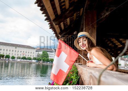 Young female traveler standing with swiss flag on the famous wooden bridge in Lucerne city in Switzerland. Having great vacations in Switzerland