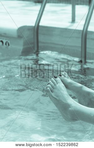 Lower body of a woman getting wet in the pool