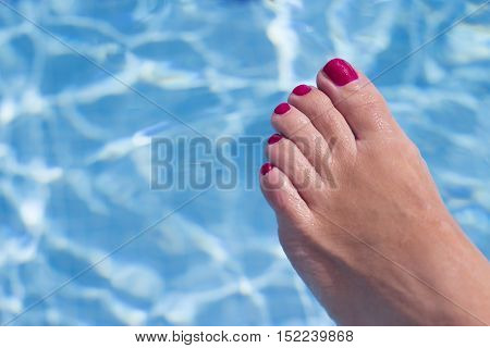 Woman feet in the pool. Red nails.