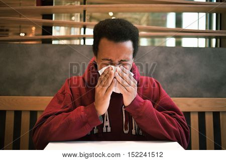 The dark-skinned man blowing his nose in a cafe. African American cold