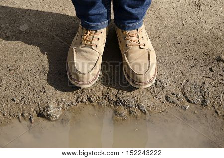 Man legs and shoes andre flected in puddle