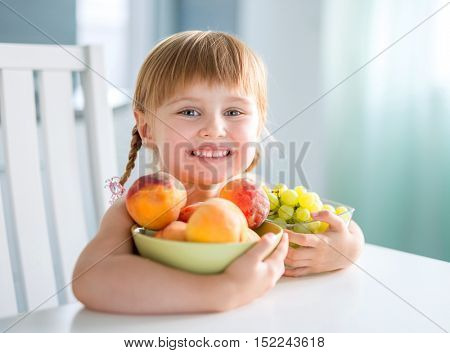 laughing little girl with peaches, grapes and water melon at the table in a kitchen