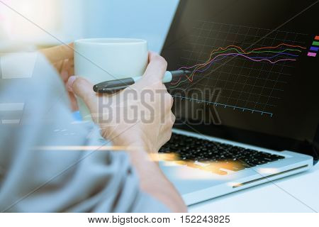 Using computer in office with a cup of coffee,Young woman working on a laptop computer while enjoying a cup of tea or coffee, close up side view of the notebook and selective focus.