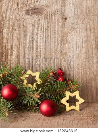 Fir branch with Christmas decorations on rustic wooden background with copy space for text.