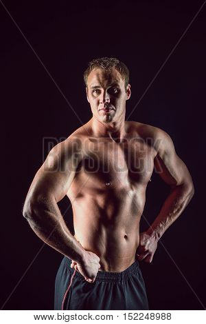 Sporty and healthy muscular strong man isolated on black background.