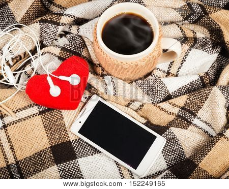 Hot coffee in a large cup, white mobile phone with headphones, soft red heart, checkered plaid on a wooden table surface