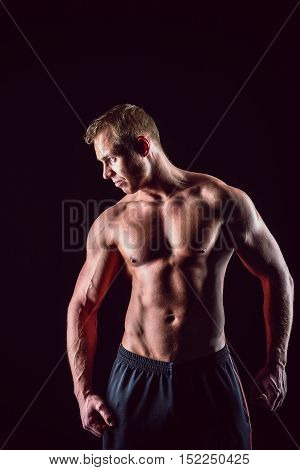Muscular, strong and sexy man isolated on black background.