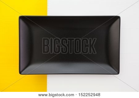 Empty black ceramic dish on over white and yelloe wooden table rectangle dish
