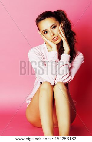 young pretty slim brunette modern woman on pink background fashion clothers emotional posing, lifestyle people concept close up