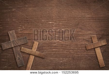Wooden cross on brown old tabletop or wall surface.
