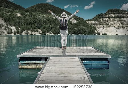 Woman stay on pier, mountains lake at sunday time.