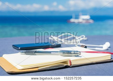 Opened empty notepad is on the table with phone and headphones at the tropical sea background and philippine boat on his surface. At sunny day under cloudy sky