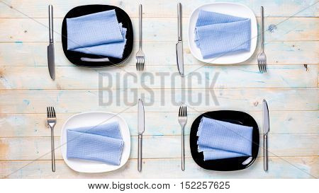 perfect table setting with black and white plates and silverware for four persons , top view