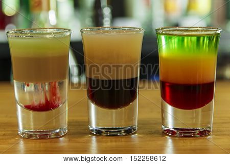 Several different alcohol multi colored shots in bar