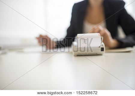 Conceptual business scene with adding machine calculator in foreground and obscured worker in background. Includes copy space.