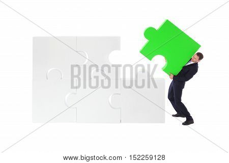 Business man assembling jigsaw puzzle isolated on white background