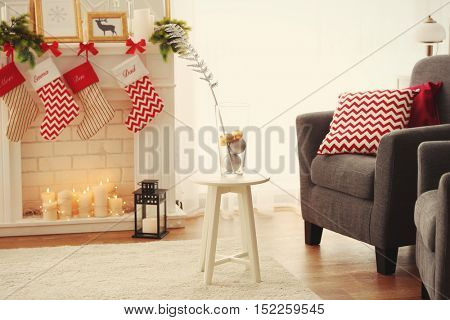 Stool with glass vase in living room decorated for Christmas