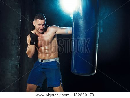 Male Athlete boxer punching a punching bag with dramatic edgy lighting in a dark studio