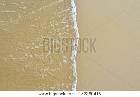 Sea sand background. Close up texture with wet sand and wave